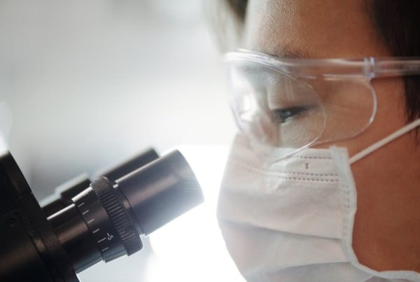 A researcher looks into a microscope during lab work and research.