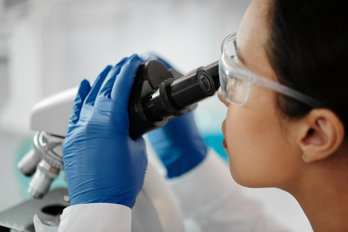 Woman looking through a microscope in a biotech firm.